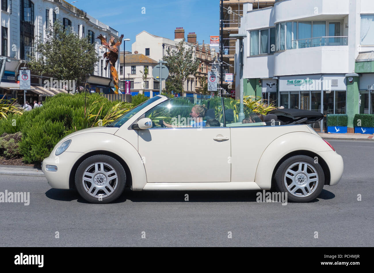 Beige convertible Volkswagen Beetle Cabriolet car from 2005, with the top down, on a road in Summer in West Sussex, England, UK. - Stock Image