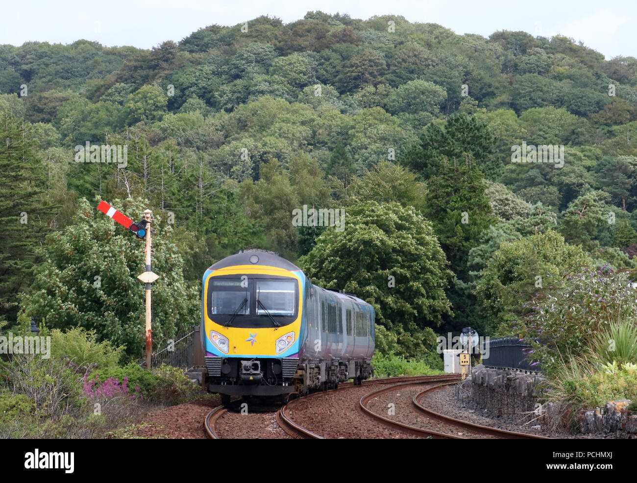 Class 185 diesel multiple-unit train in TransPennine express livery approaching Grange-over-Sands station with passenger service to Manchester Airport. - Stock Image