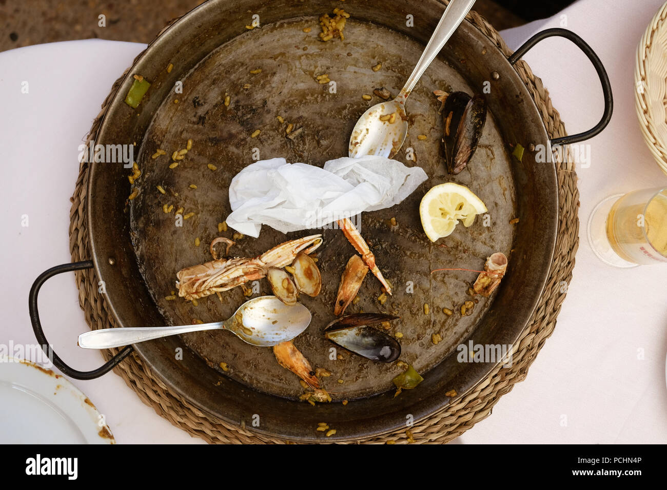 An already eaten up paella pan with two spoons. Parts of crabs and clams are laying around in the old pan. Stock Photo