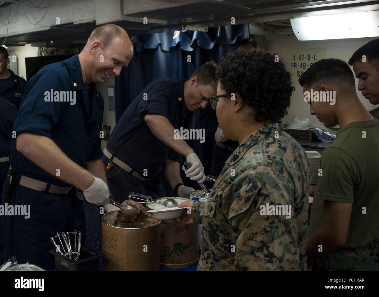 180727-N-ZK016-0004  ATLANTIC OCEAN (July 27, 2018) Officers serve ice cream to Sailors and Marines during an ice cream social on the messdecks aboard the Wasp-class amphibious assault ship USS Iwo Jima (LHD 7), July 27, 2018. Iwo Jima, homeported in Mayport, Florida, is conducting naval operations in the U.S. 6th Fleet area of operations in support of U.S. national security interests in Europe and Africa. (U.S. Navy photo by Mass Communication Specialist 3rd Class Joe J. Cardona Gonzalez/Released) Stock Photo