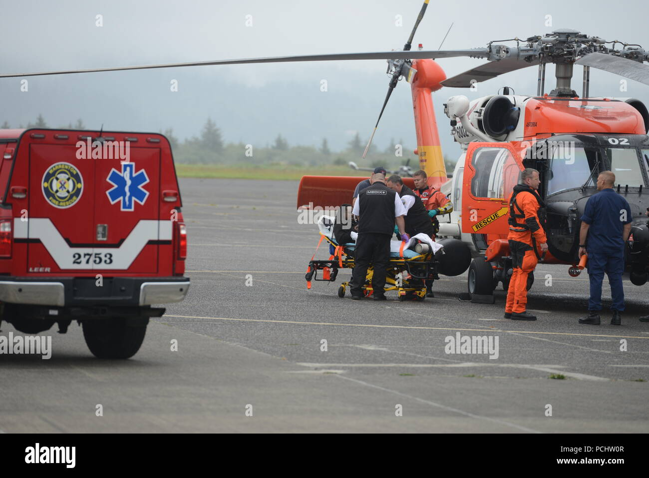 Paramedics from MEDIX ambulance and Warrenton Fire and Rescue receive a patient from a Sector Columbia River MH-60 Jayhawk aircrew at the sector's base in Warrenton, Ore., July 31, 2018.    The patient was medically evacuated off of the commercial fishing vessel Zena D 100 miles off the Pacific City, Ore., coast after he experienced trouble breathing and numbness in his extremities.    U.S. Coast Guard photo by Petty Officer 1st Class Levi Read. - Stock Image