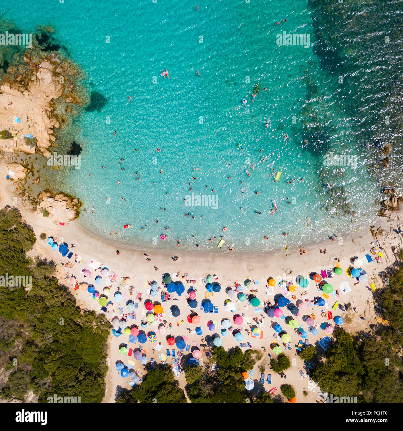 View from above, aerial view of an emerald and transparent Mediterranean sea with a white beach full of beach umbrellas and tourists who relax and swi - Stock Image