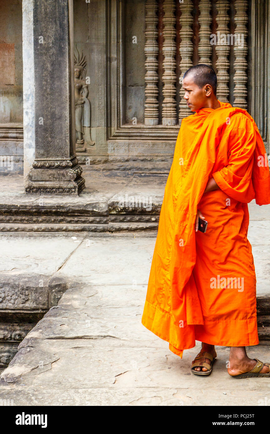 Angkor Wat, Cambodia - 11th January 2018: Monk stood by a bas relief picture. Monks can often be seen around the complex. - Stock Image