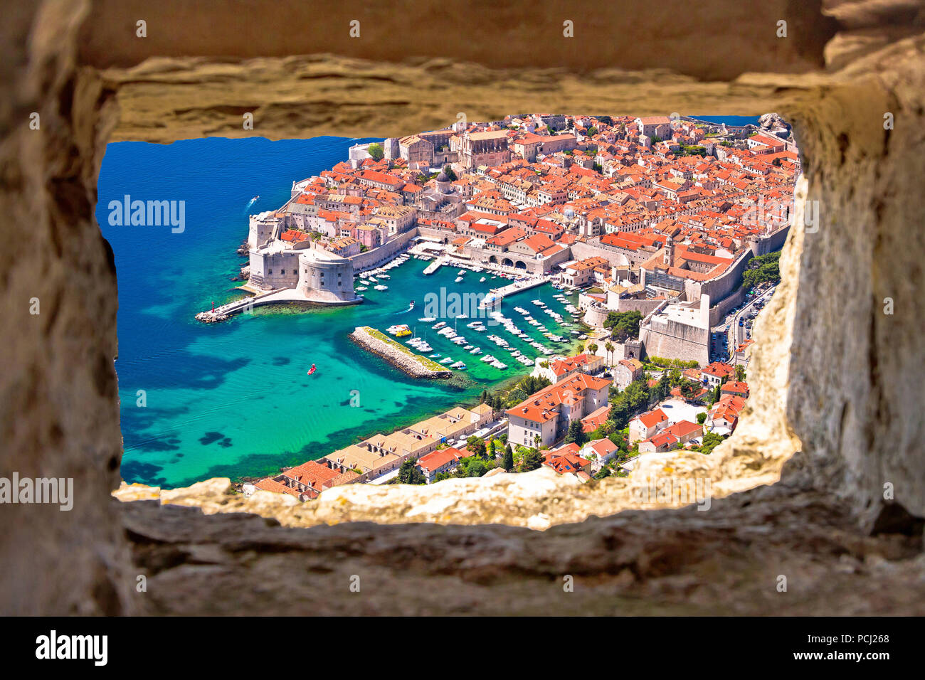 Dubrovnik historic city and harbor aerial view through stone window from Srd hill, Dalmatia region of Croatia Stock Photo