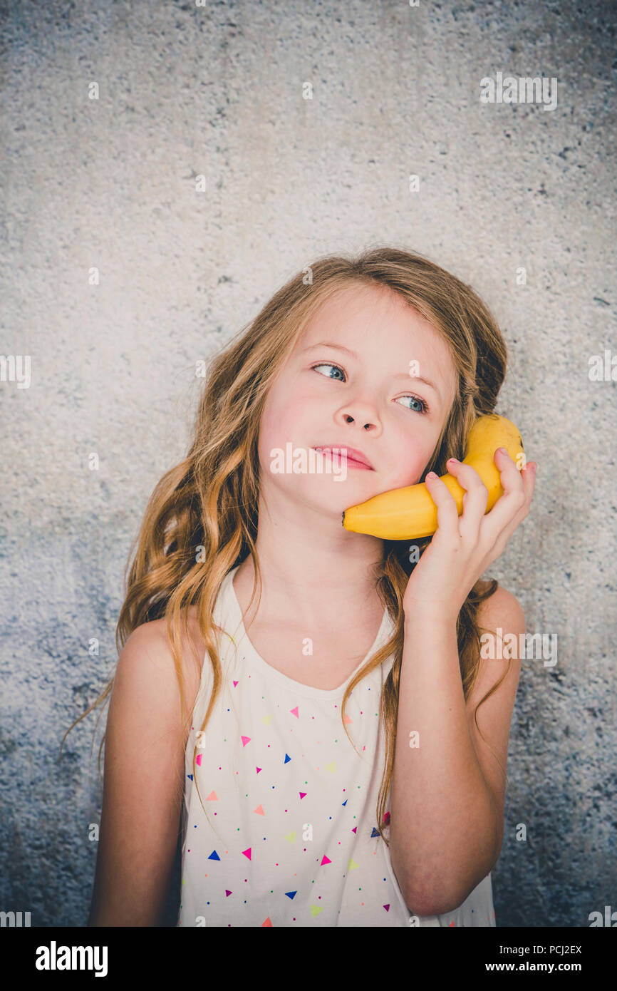 blond, Pretty girl is doing phone call with a banana - Stock Image