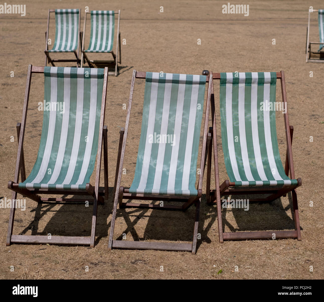 Deck chairs with green and white stripes on dead grass in a parched Hyde Park, London during the heatwave, July 2018. - Stock Image