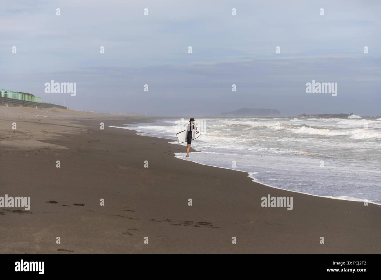 Surfer on the beach; Chigasaki, Kanagawa Prefecture, Japan - Stock Image