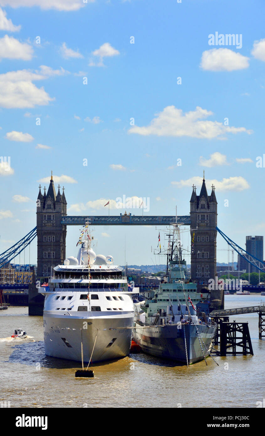 Silver Wind cruise ship moored next to HMS Belfast on the River Thames, London, England, UK. August 2018 Tower Bridge behind Stock Photo
