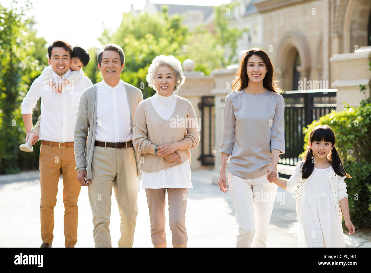Happy Chinese family strolling outside - Stock Image