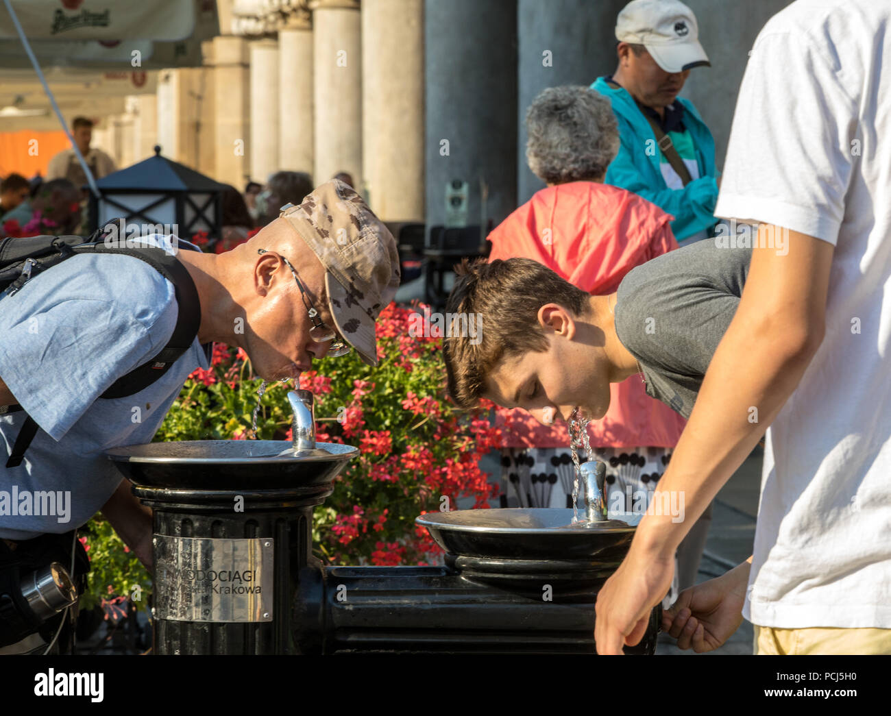 Cracow, Poland - July 5, 2018: Woman is refreshing at fountain in sweltering hot days on Main Square in Cracow - Stock Image