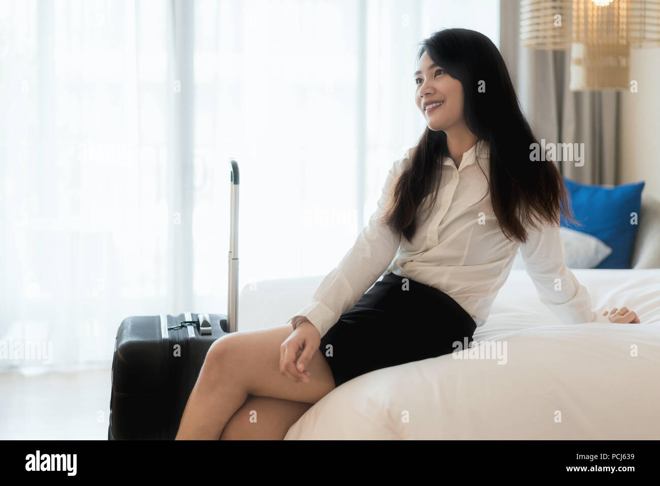 Smiling Asian business woman sitting on bed in hotel room. Business travel concept. - Stock Image