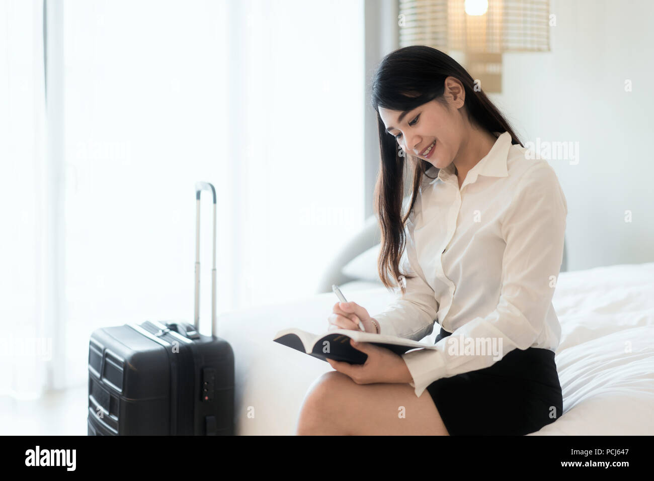Close up of a happy beautiful Asian business woman smiling cheerfully resting at her hotel suite during business trip making notes and thinking strate - Stock Image