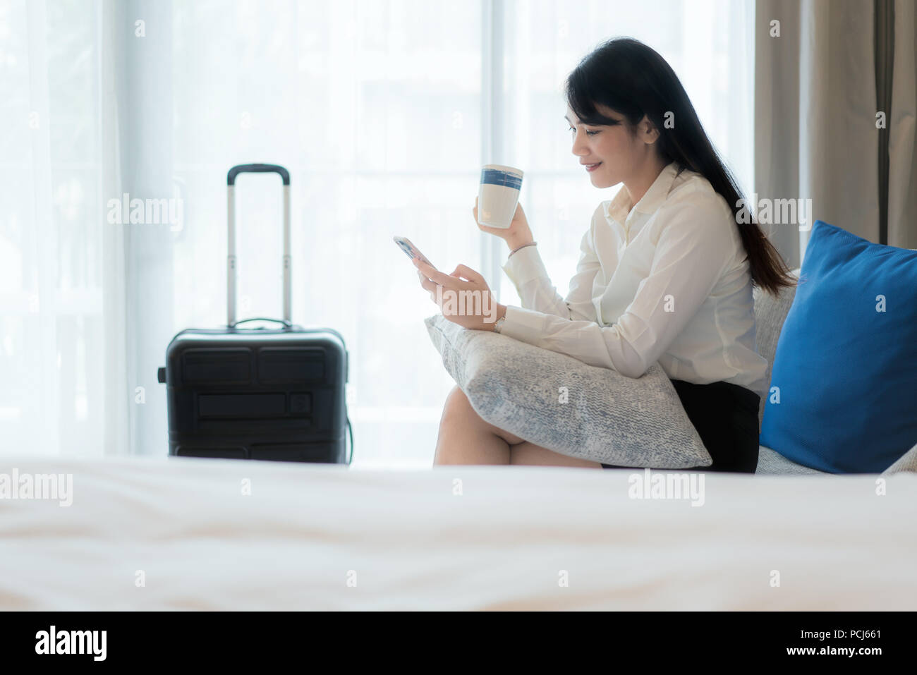 Beautiful Asian young smiling businesswoman in suit drinking coffee and using mobile phone while sitting on the sofa in hotel room. Business travel. - Stock Image