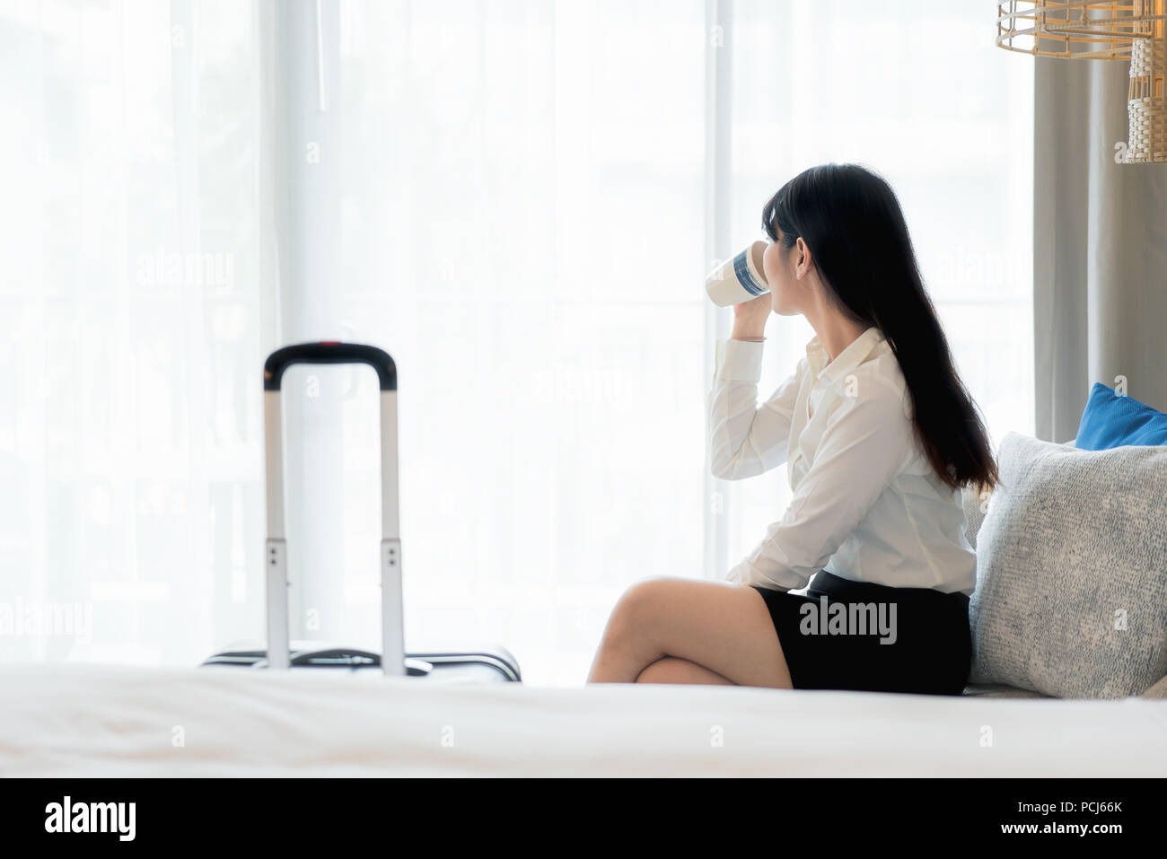 Relaxing after hard working day. Beautiful Asian young smiling businesswoman in suit drinking coffee and looking away while sitting on sofa in hotel r Stock Photo