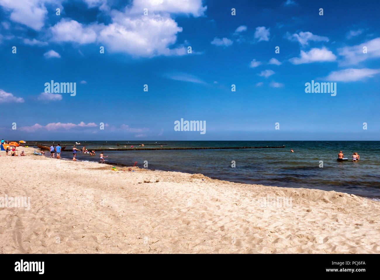 Germany Loddin,Stubbenfelde Beach. Coastal bathing resort on the island of Usedom on the Baltic Sea. Sandy beach, people swimming in tranquil sea. - Stock Image