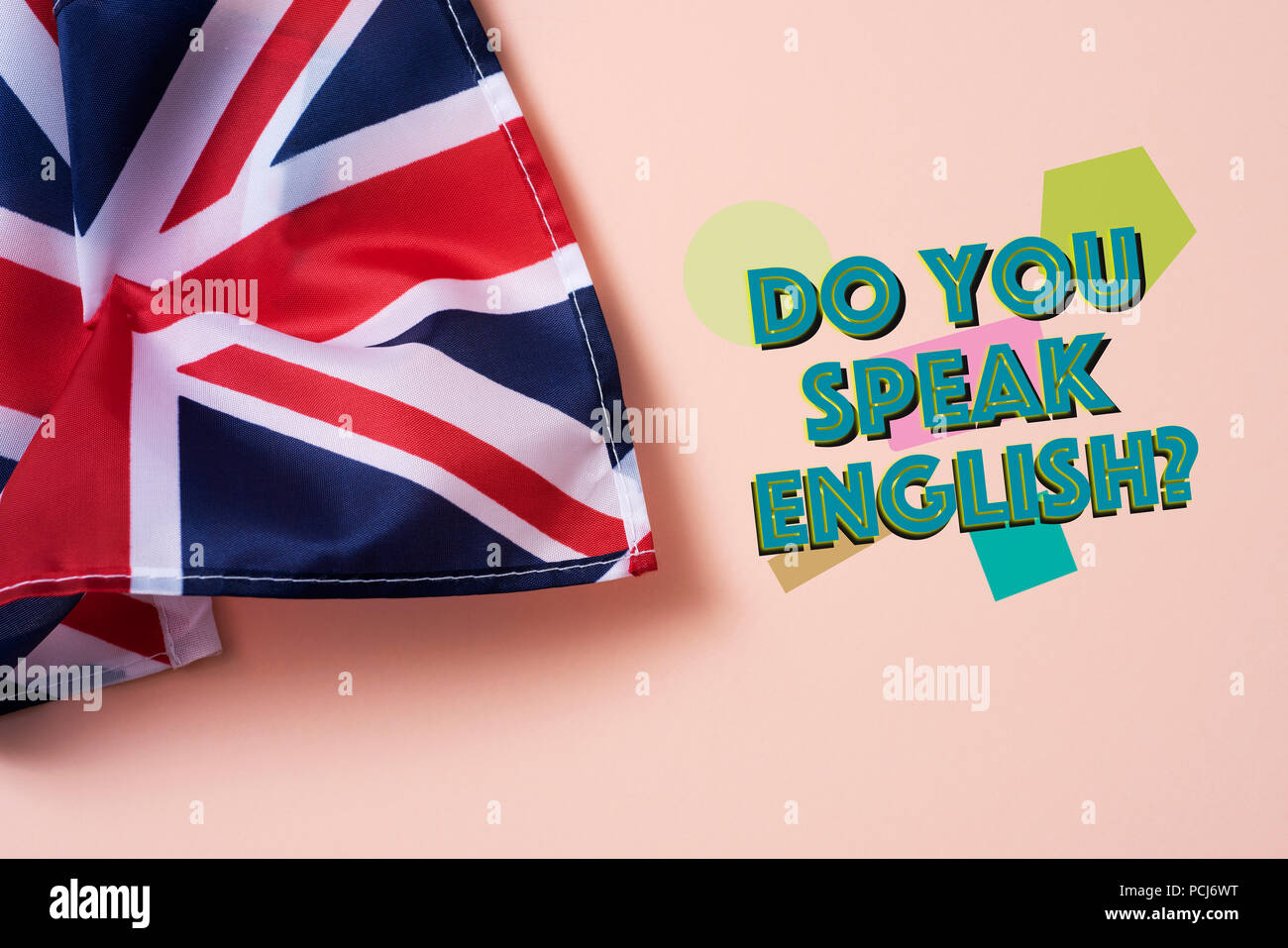 a flag of the United Kingdom and the question do you speak English? on a salmon pink background Stock Photo