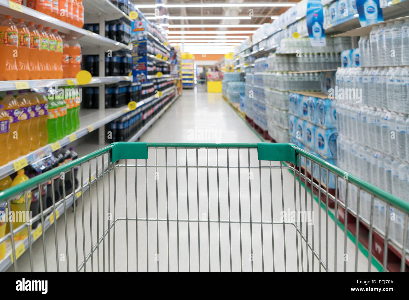 Abstract blurred photo of store with trolley in department store bokeh background. Supermarket aisle with empty green shopping cart - Stock Image