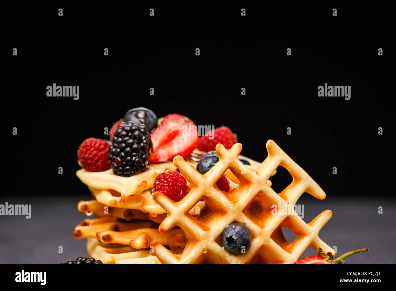 Photo of fresh viennese waffles with berries pouring honey against blank background - Stock Image