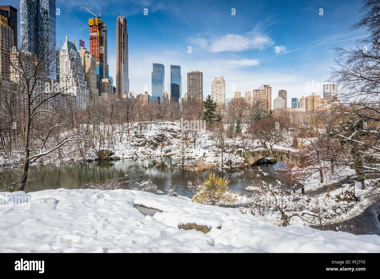 Central park in winter, view to Manhattan buildings and Gapstow bridge, New York City - Stock Image