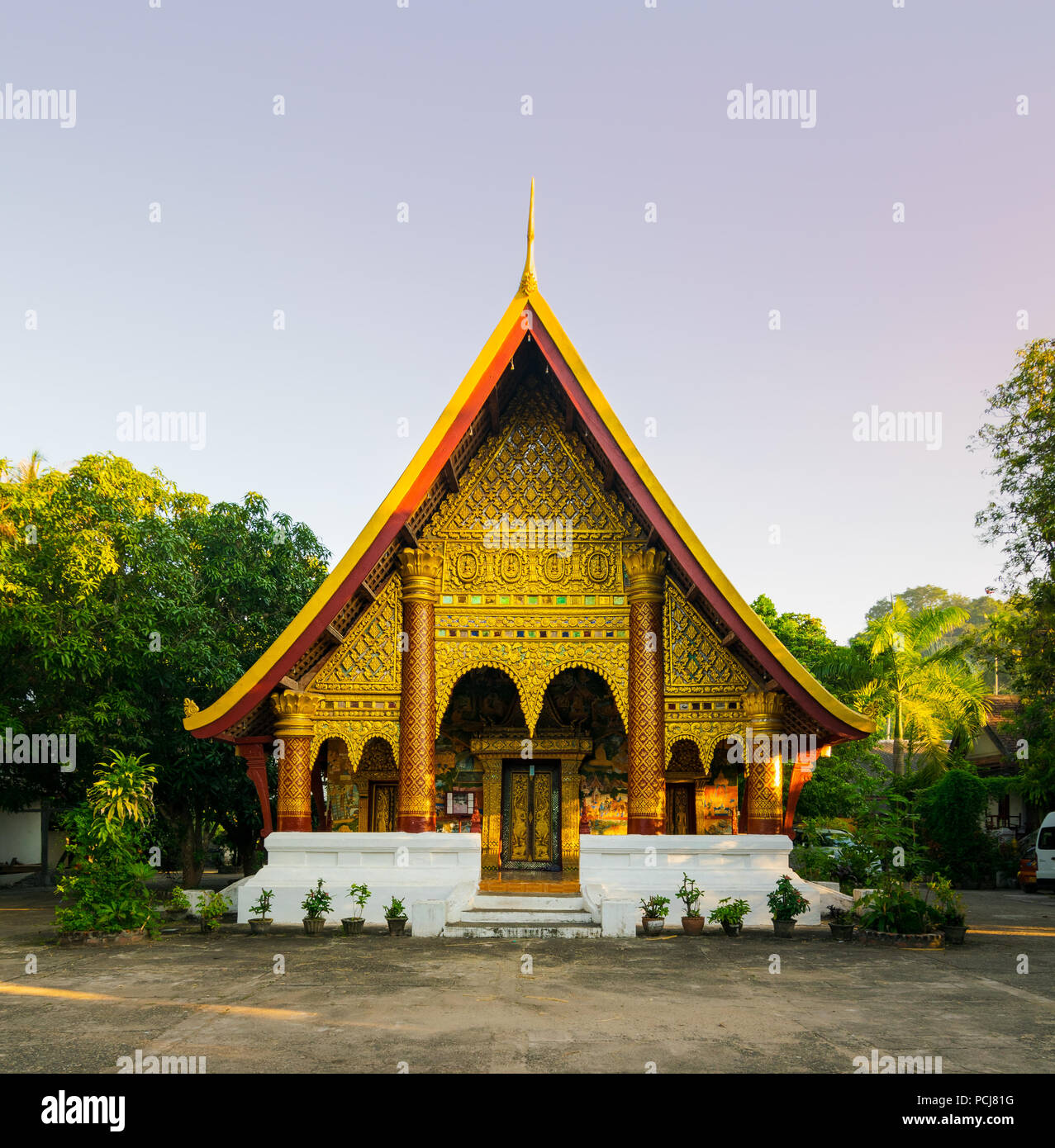 Buddhist temple with golden carved decorations and tiled roof in Vientiane, Laos - Stock Image