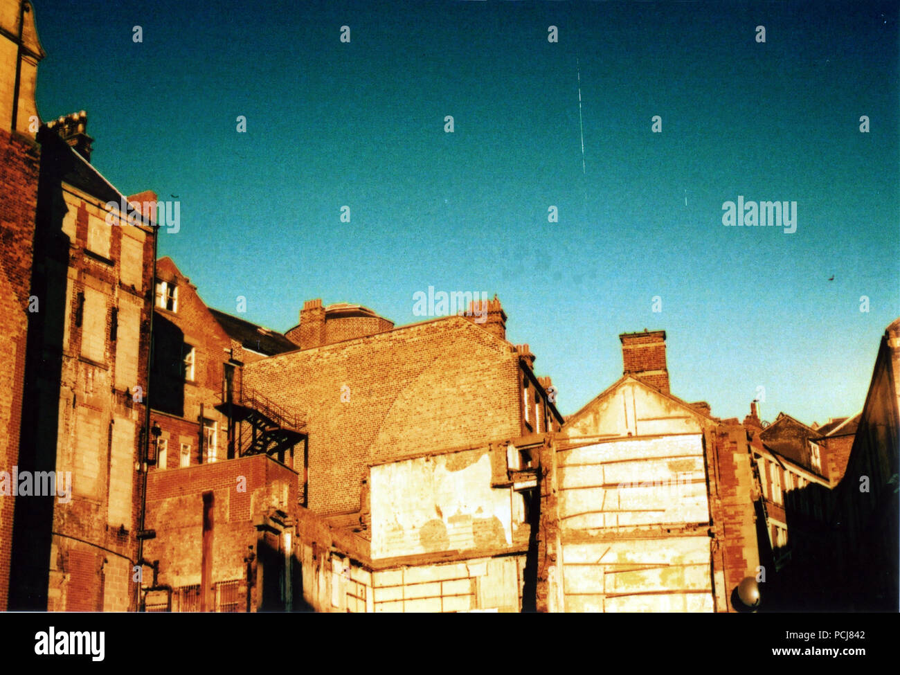 Back of part demolished buildings during renovations in Newcastle. Cross Processed - Stock Image