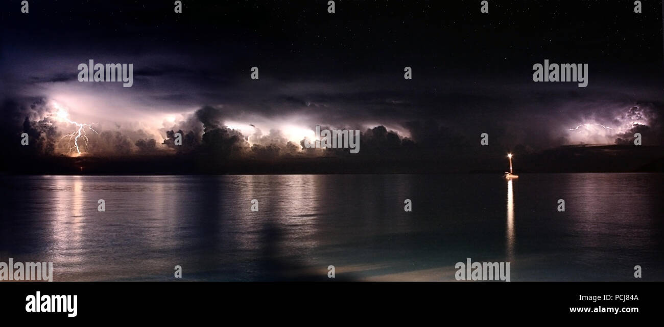 Multiple forks of lightning during a thunderstorm over the ocean. Panoramic with lone boat lit up at night - Stock Image