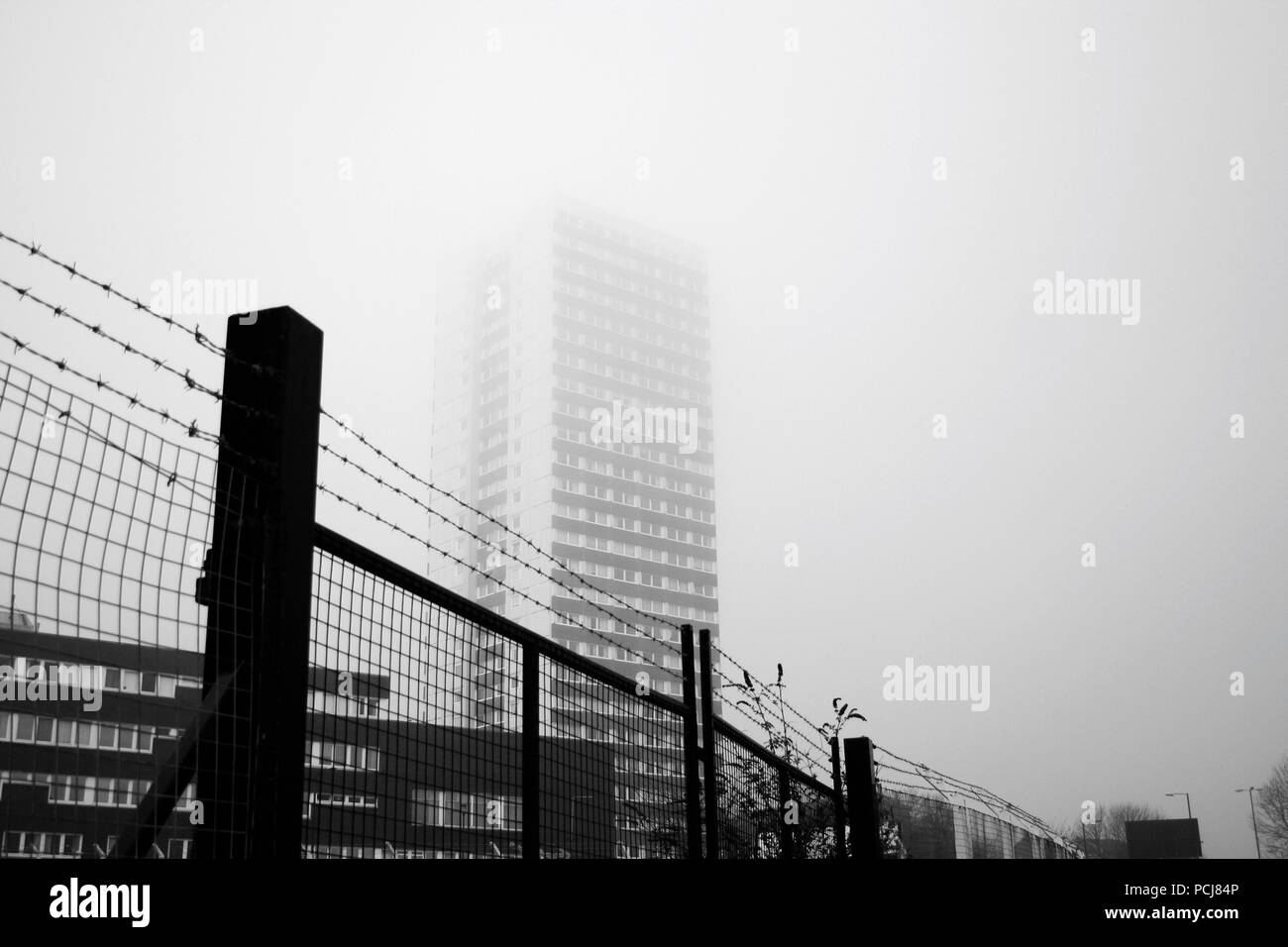 High rise flats disappearing into fog behind a barbed wire fence Stock Photo