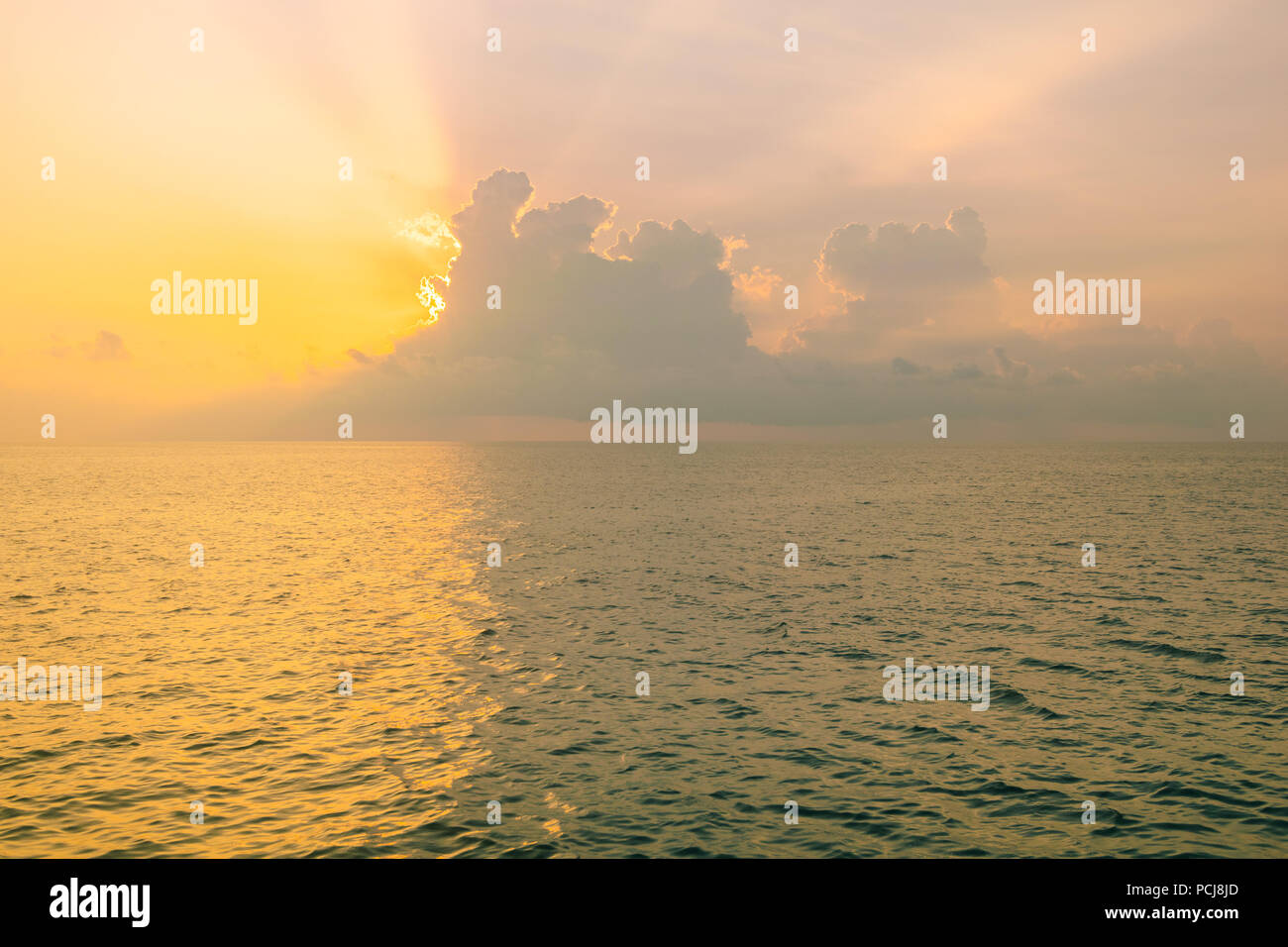 The sun is rising being storm clouds and filtering through, over the Andaman sea in Thailand. Stock Photo