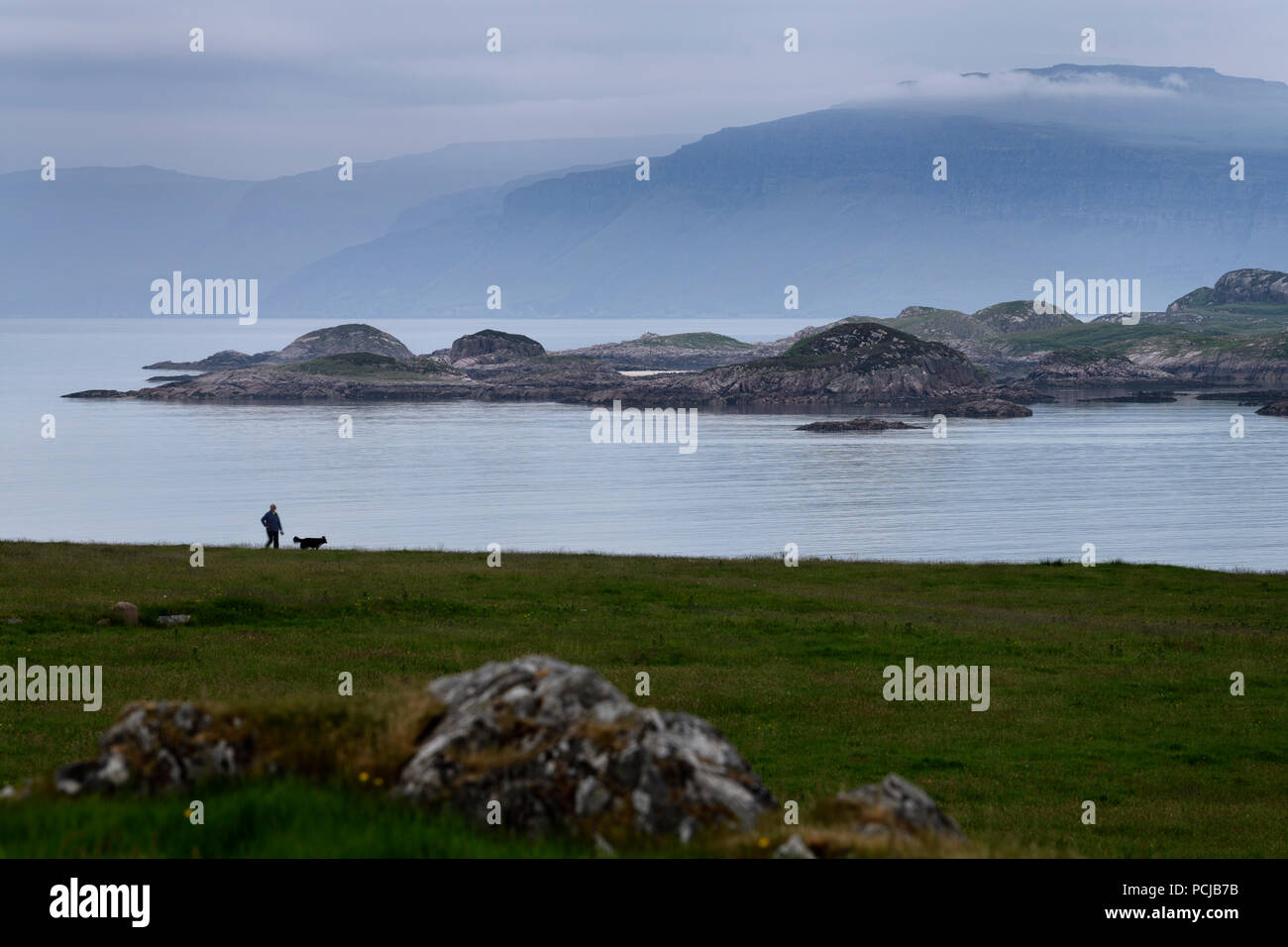 Woman walking her dog with view of Isle of Mull cliffs and Ben More mountain over Sound of Iona from Isle of Iona Abbey at dusk Scotland UK - Stock Image