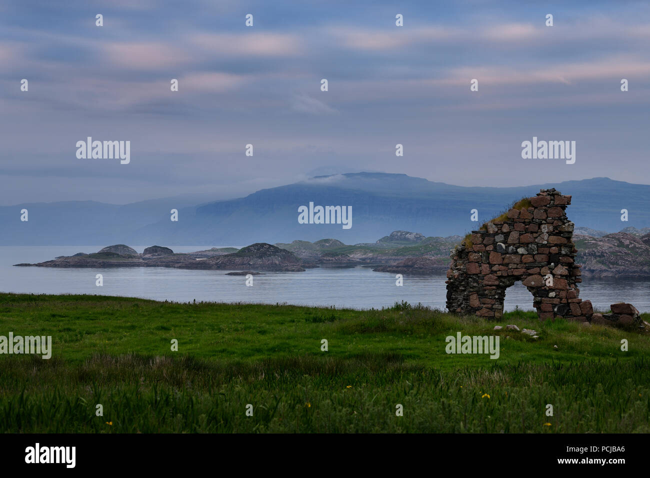 Granite stone ruins of the Bishop's House next to Iona Abbey at dusk on Isle of Iona with view over Sound of Iona to Isle of Mull mountains Scotland - Stock Image