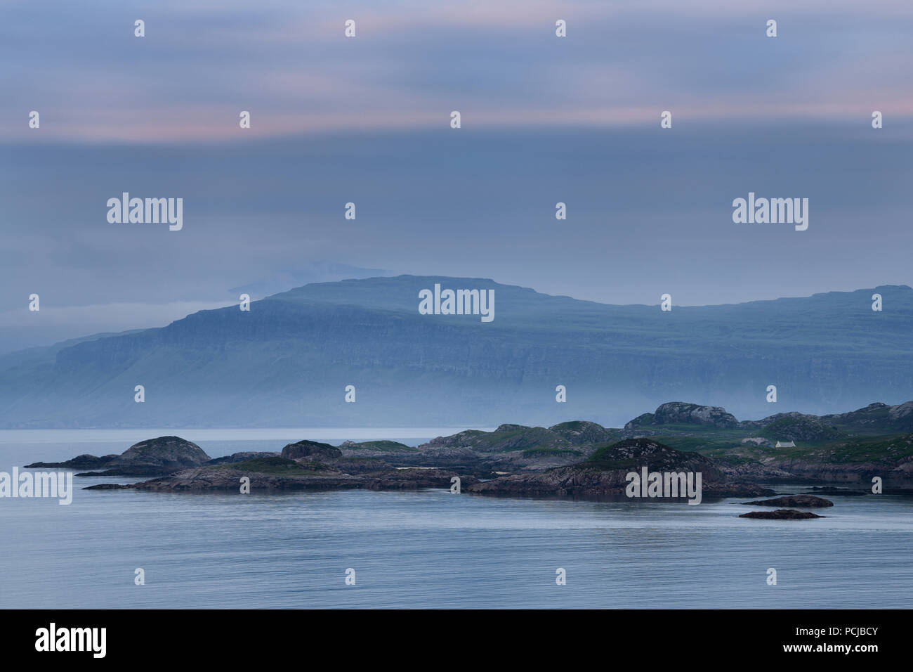 View of Isle of Mull cliffs and Ben More mountain over Sound of Iona from Isle of Iona Abbey at dusk Scotland UK - Stock Image
