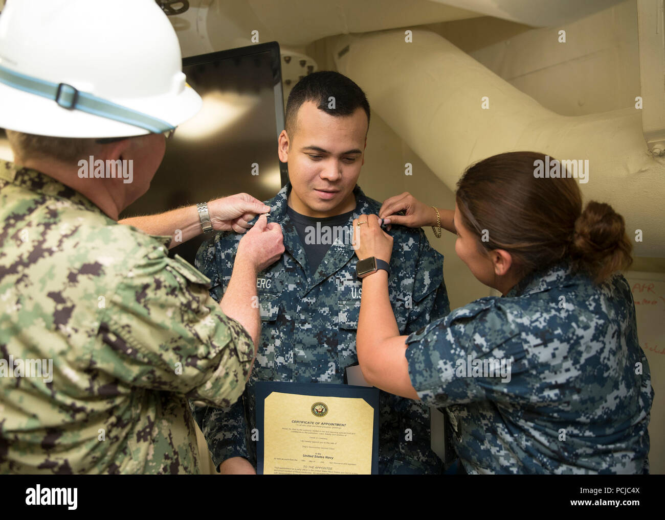 NEWPORT NEWS, Va. (July 30, 2018) -- Ship's Serviceman 2nd Class Dereck S. Lindburg, from Manila, Philippines, assigned to USS Gerald R. Ford's (CVN 78) supply department, is pinned to his Current rank by Capt. Richard McCormack, left, Ford's commanding officer, and Senior Chief Ship's Serviceman Angela Zamora, right, from Jersey City, New Jersey, during a meritorious advancement ceremony in the ship's supply office. (U.S. Navy photo by Mass Communication Specialist 3rd Class Ryan Carter) (This image has been altered by blurring out badges for security purposes) - Stock Image