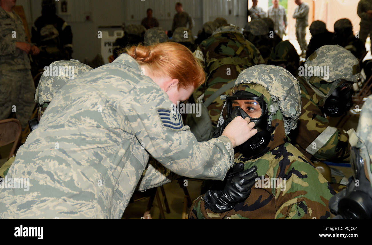 ALPENA, Mich.-- An instructor with the 127th Civil Engineering Squadron assists Tech Sgt. Chanel Daniels, 127th Force Support Squadron, in adjusting her gas mask during Battle Lab training at the Alpena Combat Readiness Training Center on July 29, 2018. During the training, Airmen of the 127th Wing, like Daniels, practiced donning and removing different levels of chemical protection equipment during an operational readiness assessment exercise. (U.S. Air Force photo by Master Sgt. David Kujawa) Stock Photo