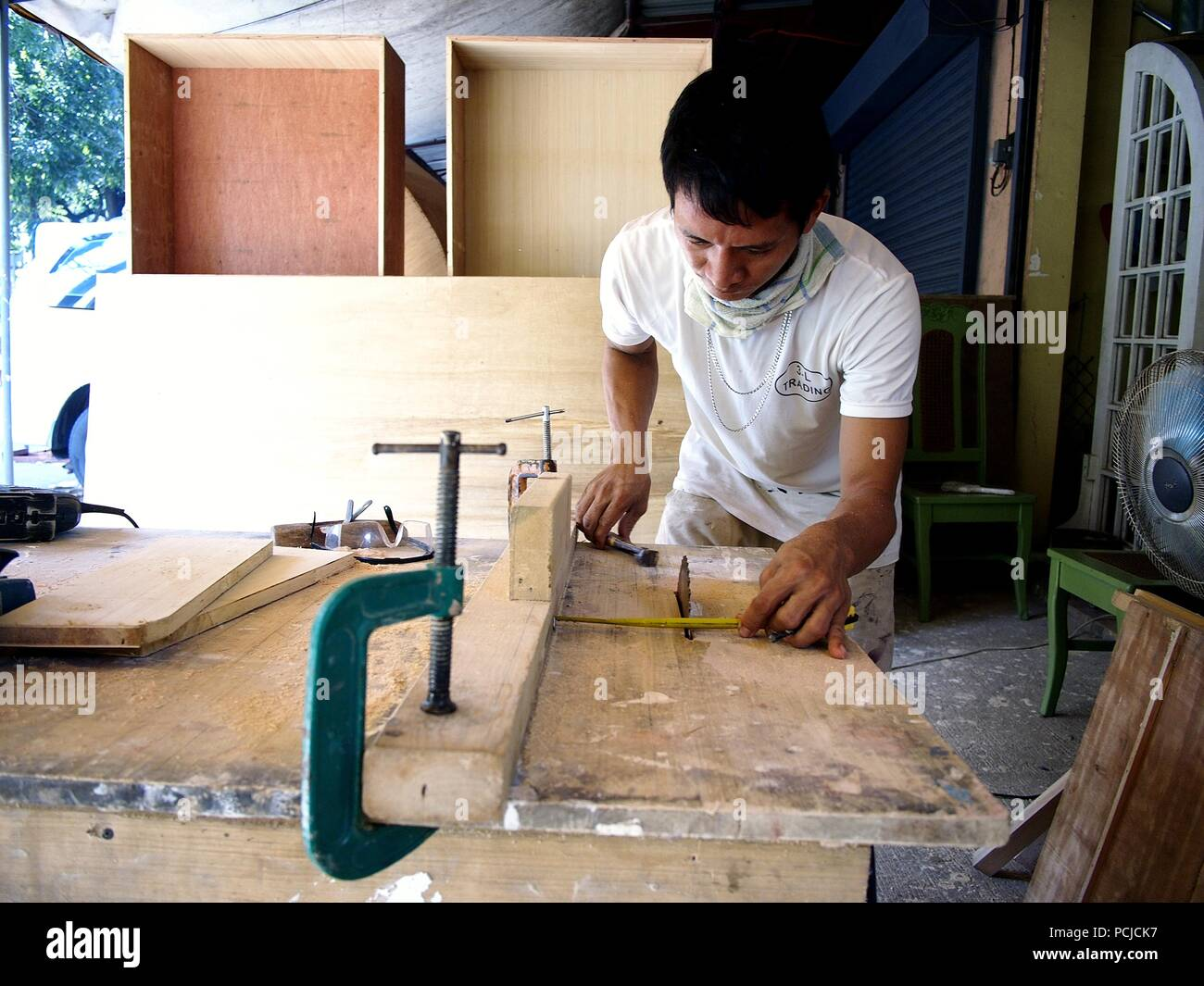 ANTIPOLO CITY, PHILIPPINES - JULY 31, 2018: A carpenter cuts wood using a table saw in his workshop. - Stock Image