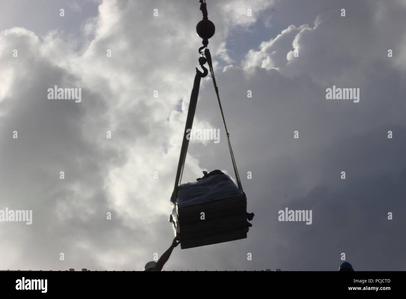 A pallet of seized cocaine hangs from a crane hook in Port Everglades, Aug. 1, 2018.  The drugs were seized during the interdiction of five suspected smuggling vessels and the recovery of two floating bile fields found off the coast of Mexico, Central and South America by Coast Guard Cutters Hamilton (WMSL-753), Alert (WMEC-630) and Venturous (WMEC-625). Coast Guard Photo by Seaman Erik Villa-Rodriguez. - Stock Image