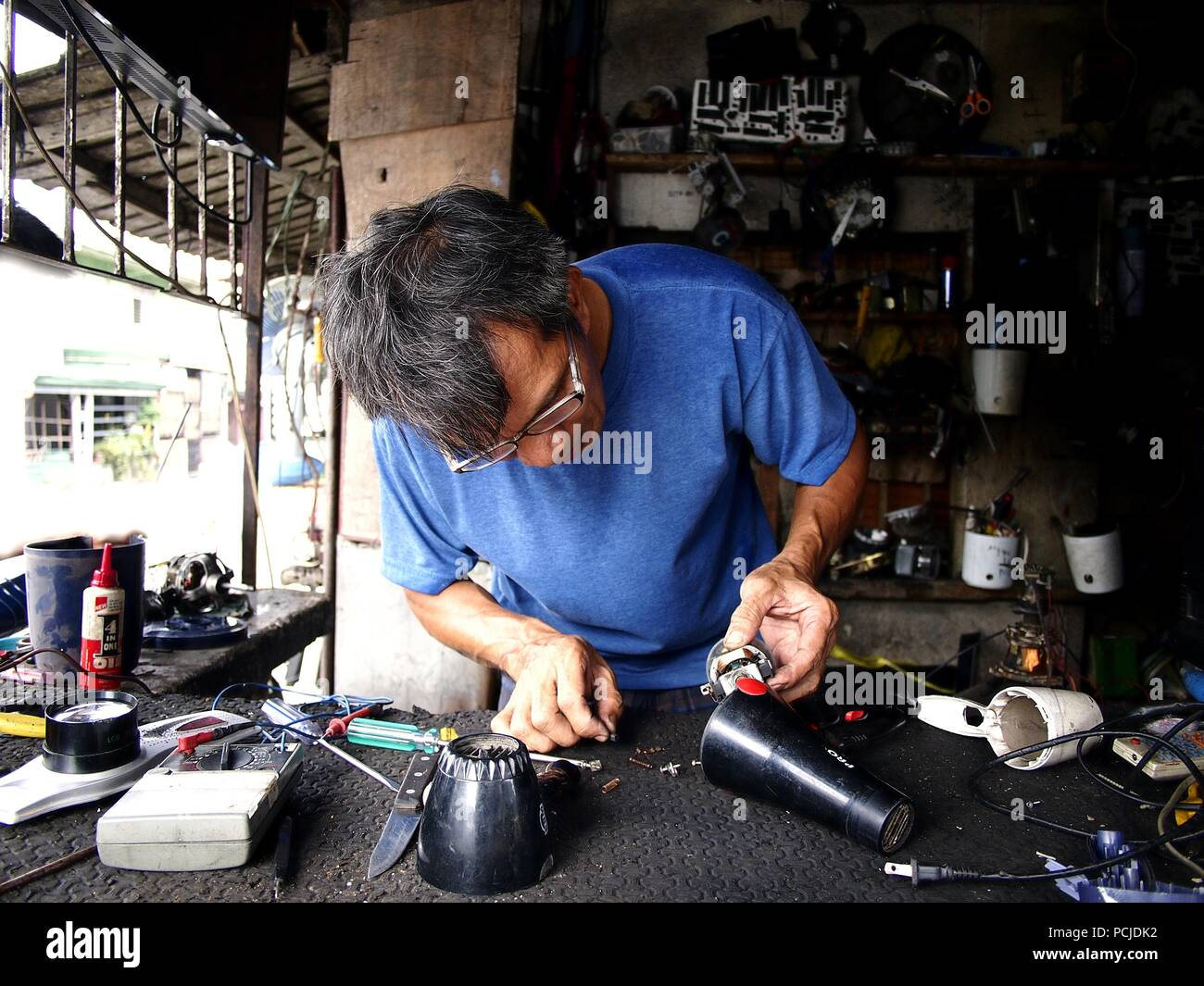 ANTIPOLO CITY, PHILIPPINES - AUGUST 1, 2018: A electrician fixes an electronic household item in his repair shop. - Stock Image