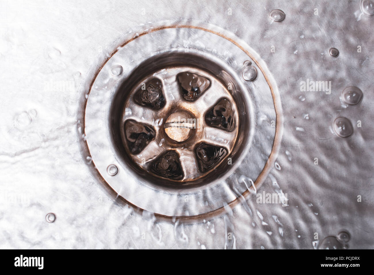 Bright Dirty Drain Of A Kitchen Sink With Flowing Water, Top Down View Stock Photo