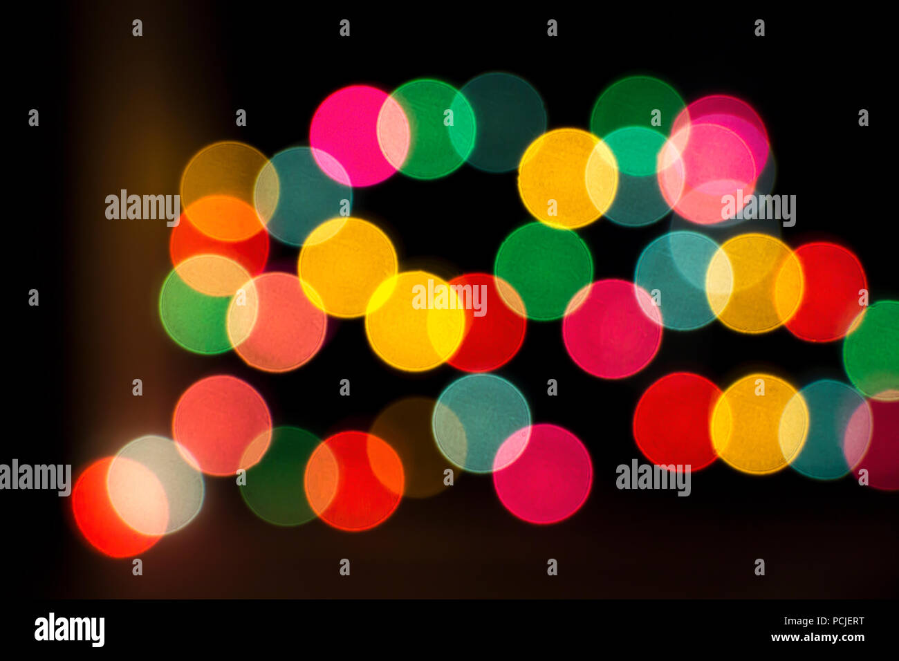 blurred bokeh colorful lights lanterns holiday new year lighting on black background christmas winter glitter shiny light bokeh in rainbow colors
