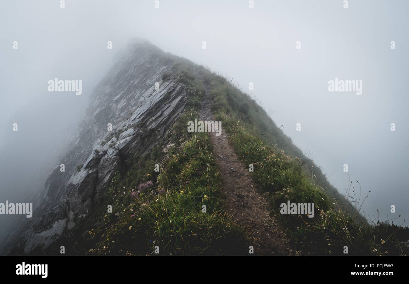 scary hiking path covered in fog on the ridge of a mountain in the swiss alps, brienzer rothorn switzerland Stock Photo