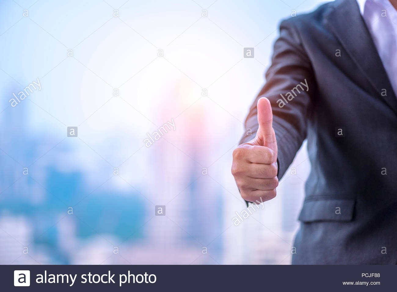 Businessman showing thumbs up with urban city background for the good job - Stock Image