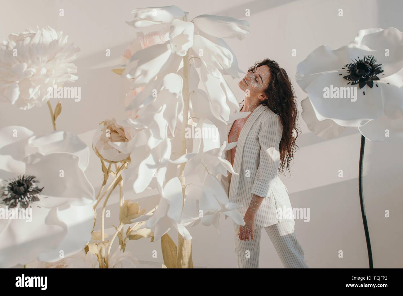 Beautiful woman covered in glitter standing by giant artificial beautiful woman covered in glitter standing by giant artificial flowers izmirmasajfo
