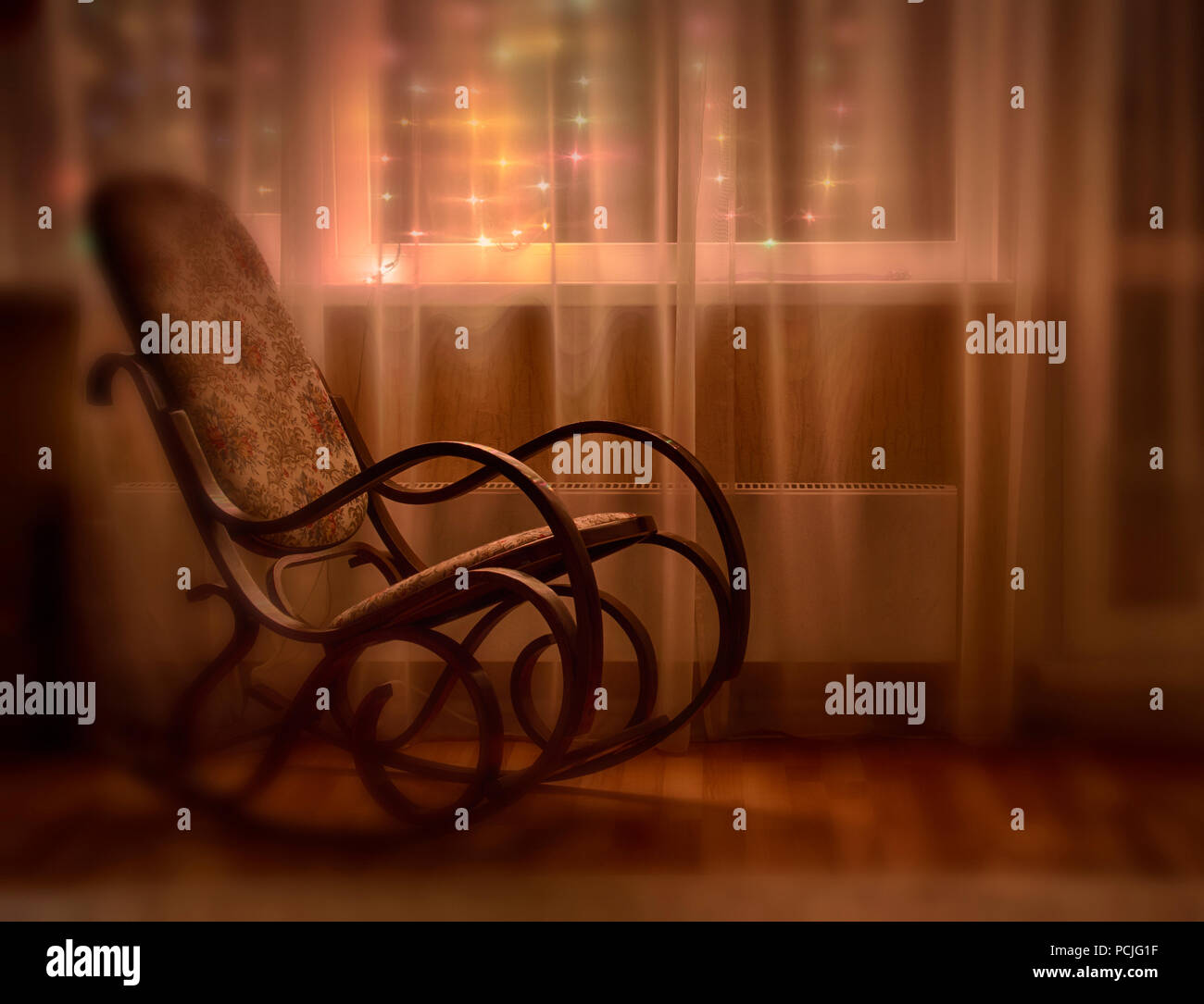 A rocking chair stands by the window in the evening light. Blurred effect. - Stock Image