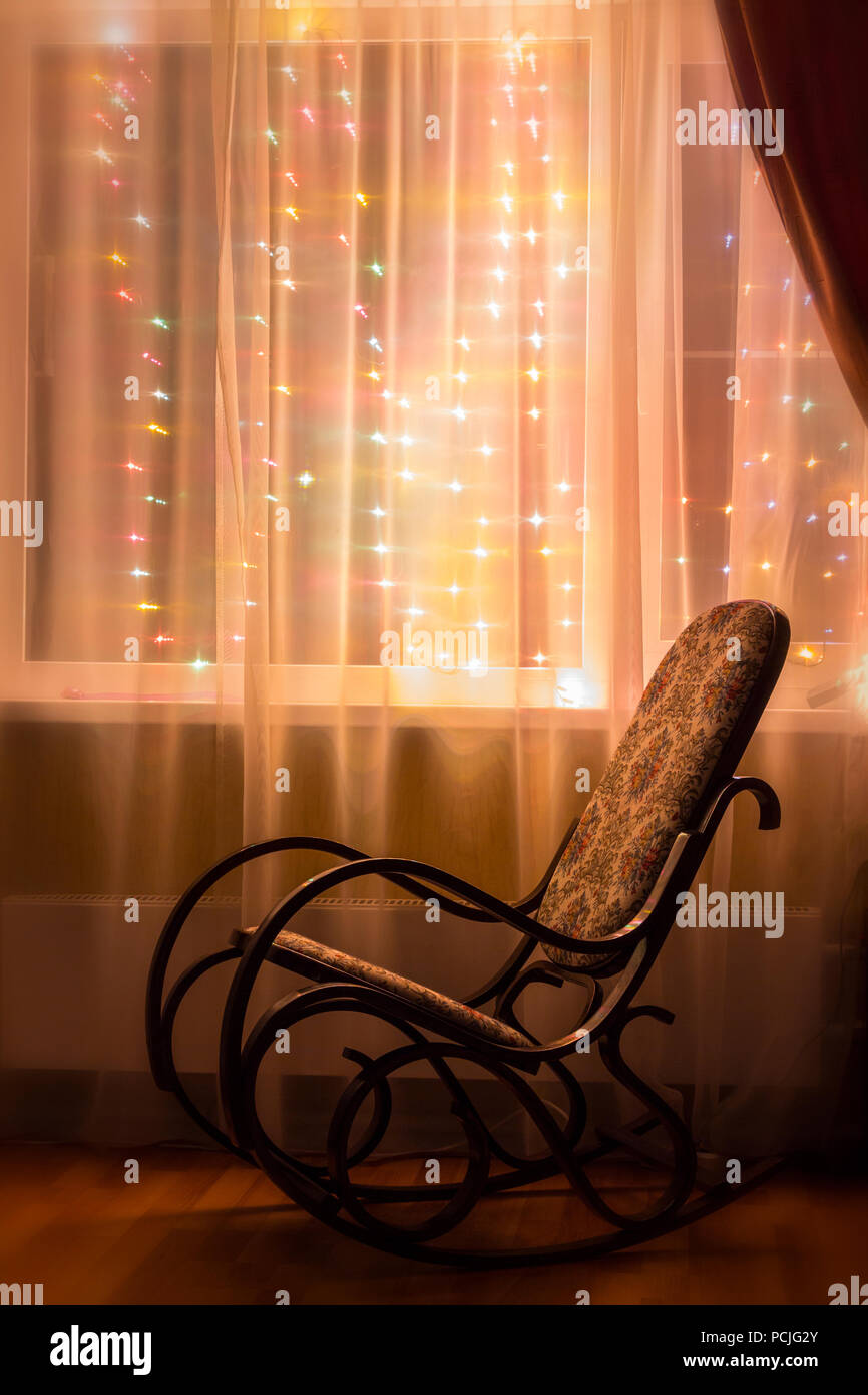 A rocking chair stands by the window in the evening light. - Stock Image
