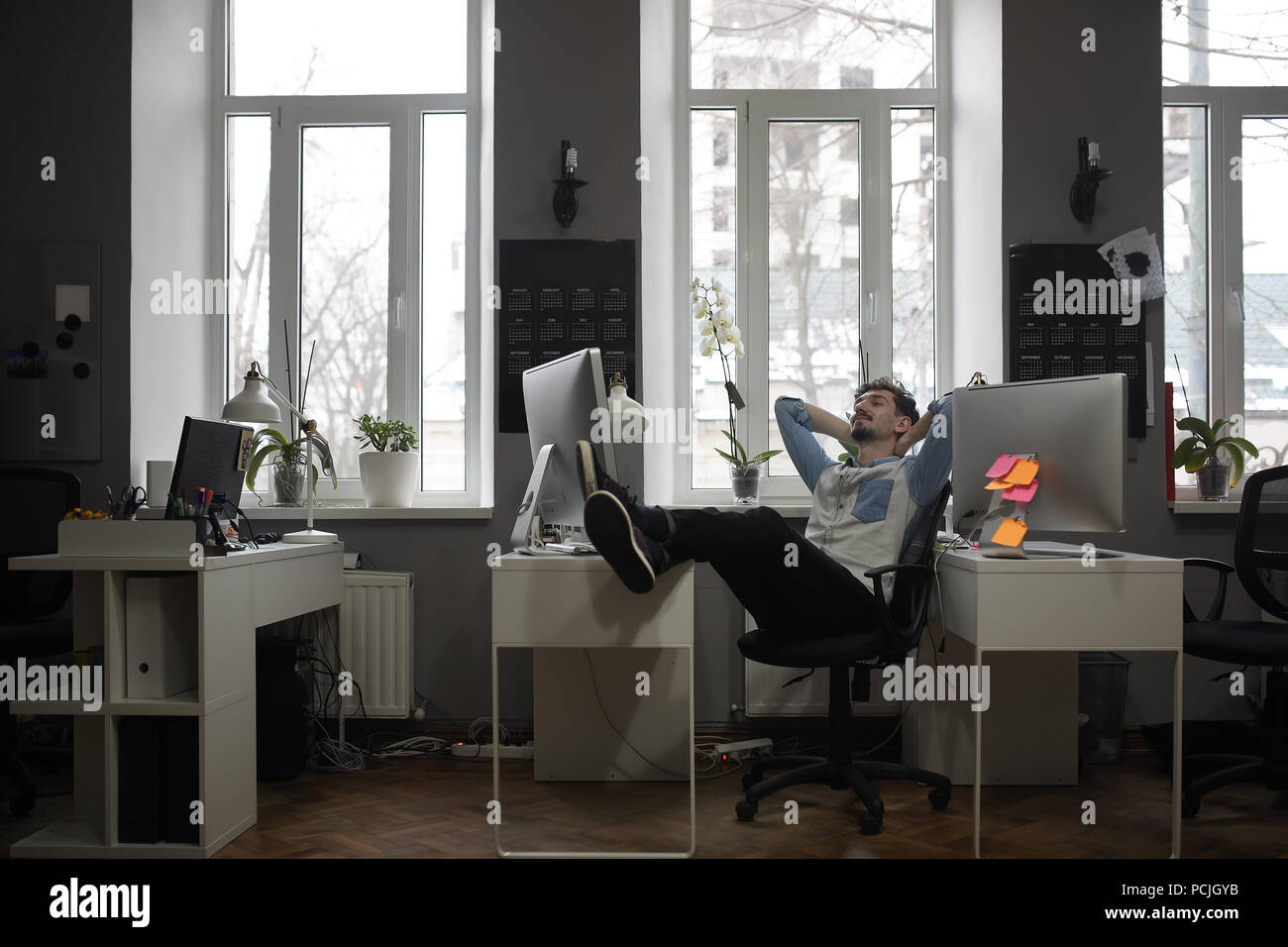 A man thinking of a vacation in a modern office while relaxing - Stock Image