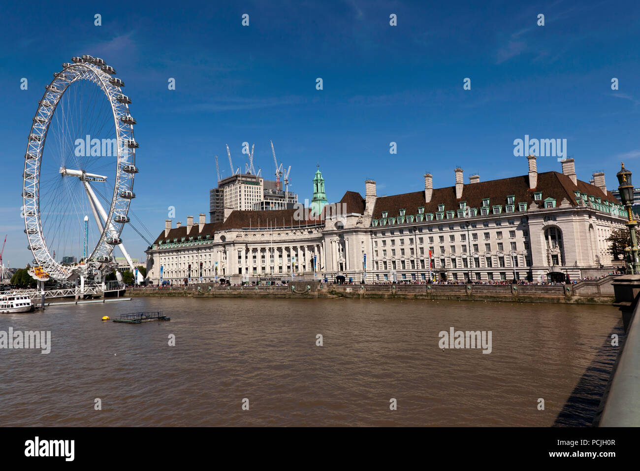 Wide-Angle view of The London Eye  and the former  London County Hall Building, as seen from Westminster Bridge, London - Stock Image
