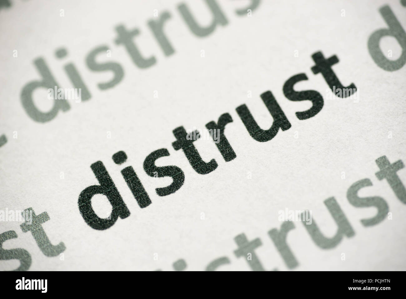 word distrust printed on white paper macro - Stock Image