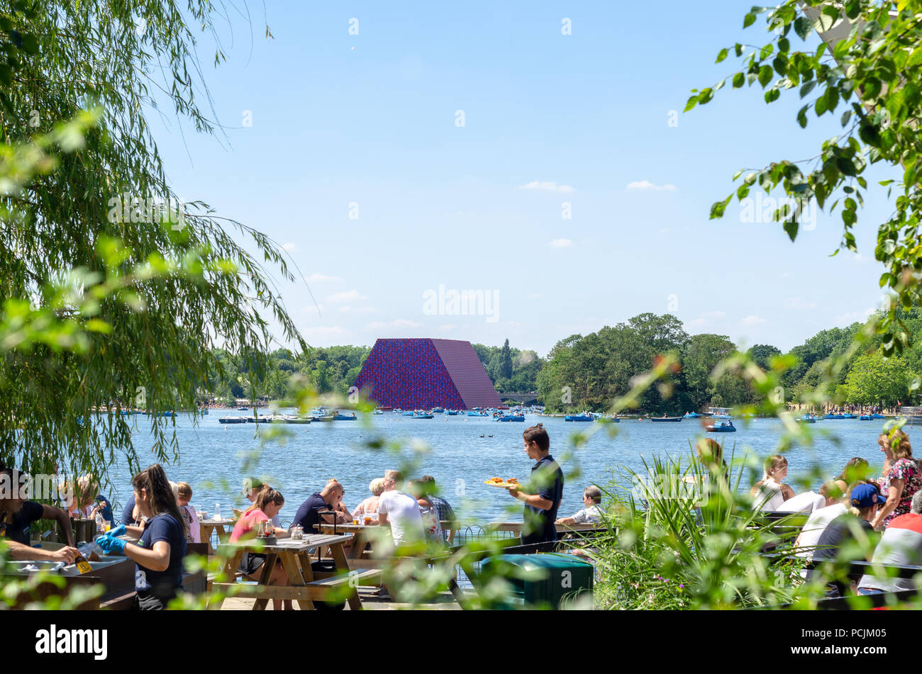 Tourists at the Serpentine at Hyde Park Christo's Mastaa floating in the background. - Stock Image
