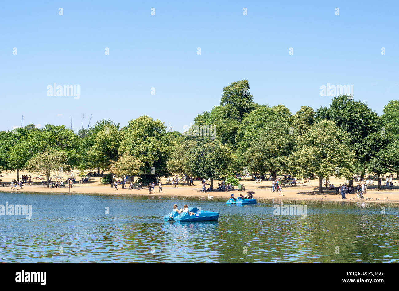 Boats on the Serpentine  at Hyde Park in during the heat wave of summer 2018 - Stock Image