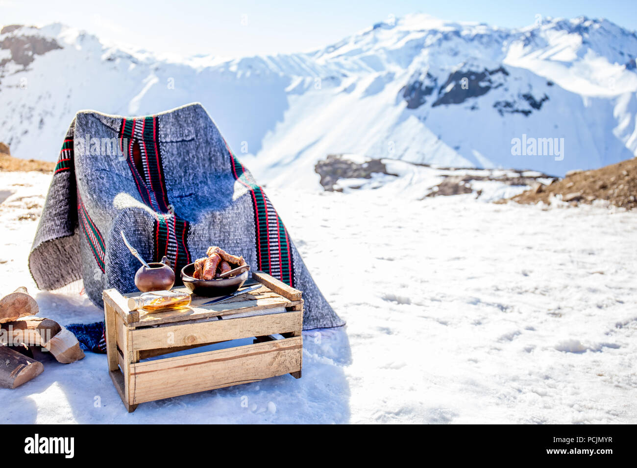 Winter picnic in chilean argentine snow mountaines Andes with hot meat food and drink yerba mate. - Stock Image