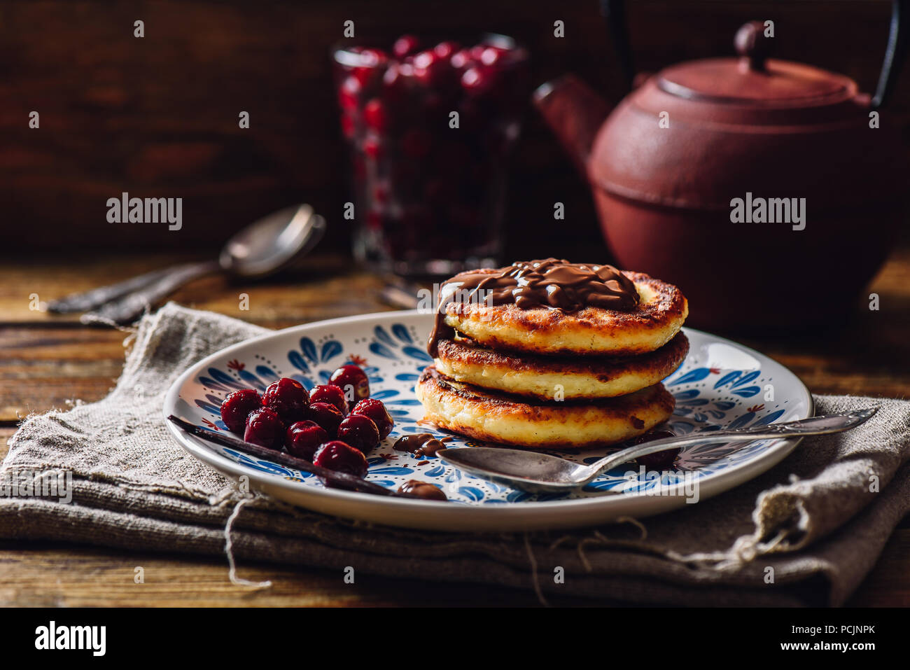 Russian Quark Pancakes with Chocolate Topping and Frozen Cherry. Tea Pot with Spoons and Glass of Berries on Background. - Stock Image